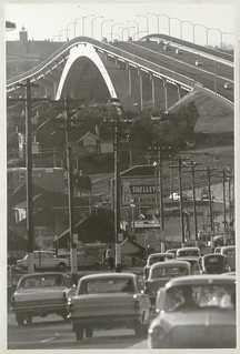Traffic and line of telegraph poles approach the Gladesville Bridge, Oct 1966