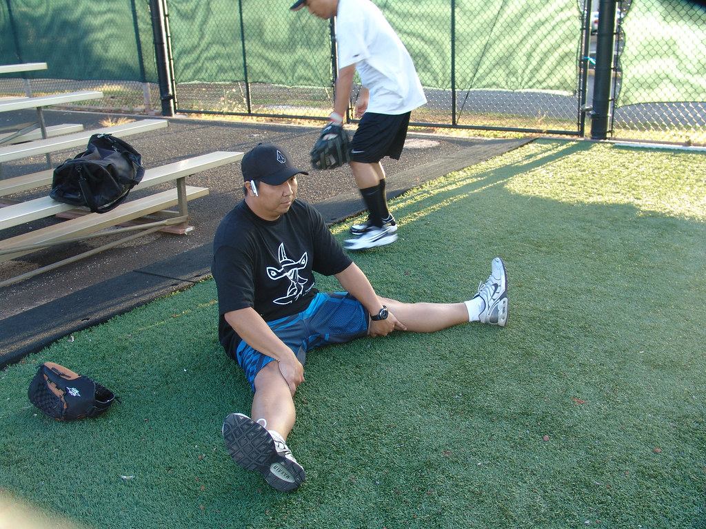 <p>Players, who are UH employees at the various campuses by day, stretched to limber up for play in the UH AUW Softball Tourment at Les Murakami Stadium on Sept. 30, 2011</p>