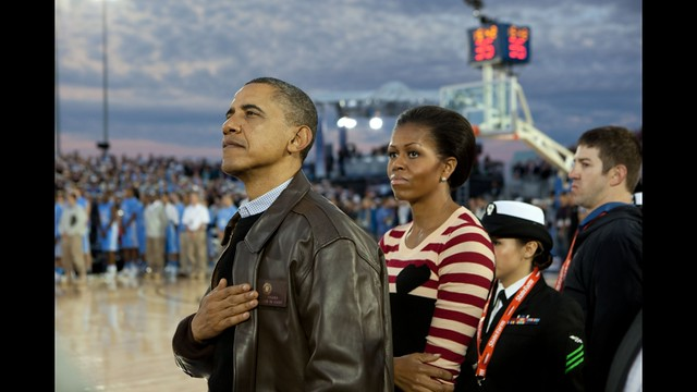 President Barack Obama and First Lady Michelle Obama watch the retiring of the colors aboard the USS Carl Vinson