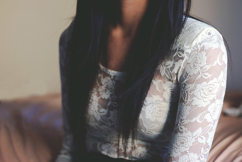 Photo of a woman wearing a white lace top with black hair--her face is out of the frame