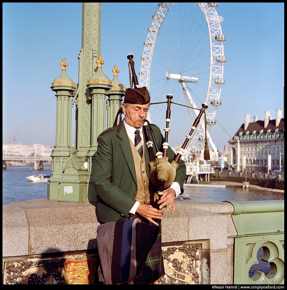 A man playing bagpipes, London