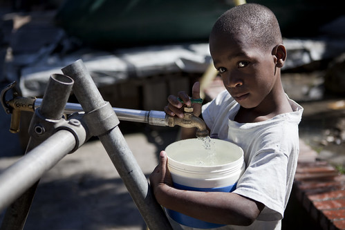 Haitian Child Collects Water in Camp for Displaced