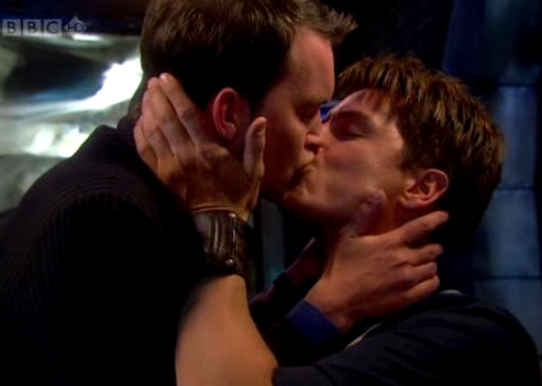 Two men kiss, holding each other's faces. One stands while the other is sitting. The background is blue with a stream of bright white light pouring in from the upper left corner. The top upper left corner reads