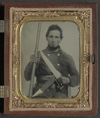 [Unidentified soldier in Confederate uniform with musket, D guard Bowie knife, and knife sheath labeled Philadelphia Avengers, N.Y.] (LOC)