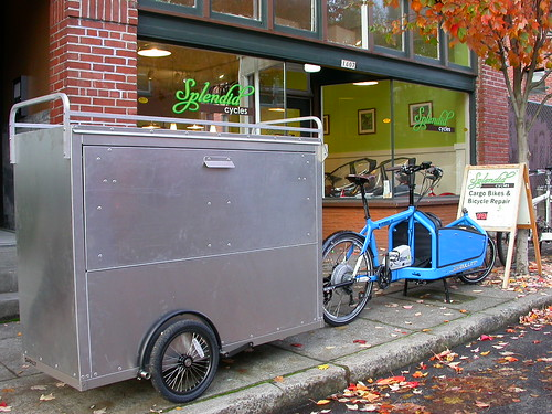 Right side view of a bike with steel bin on front, and a trailer hitched in back, on a sidewalk beside Splendid Cycles