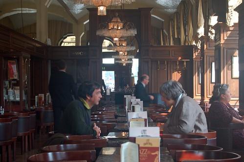 In der Bildmitte ein Paar, das bei einem Cafe im Schwarzenberger sich unterhält.
