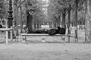 Paris Jardin des Tuileries photo de rue parc banc homme allongé qui dort noir et blanc allée