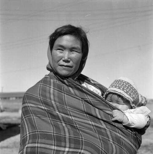 Woman drapped in a blanket carrying a baby / Femme enveloppée d'une couverture, un bébé dans les bras