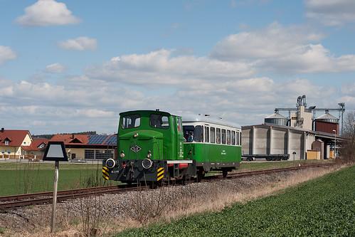 Zug P3804 hat gerade Eggmühl verlassen und passiert die Trapeztafel des Bahnhofs.  Im Hintergrund ist das Lager »Meier-Kammermeier« zu sehen.