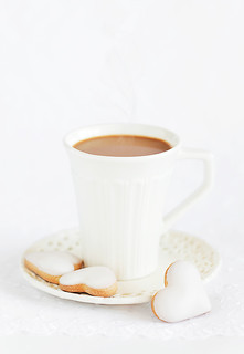 A cup of hot cocoa and homemade white chocolate frosting cookies