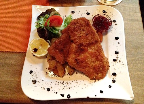 Kalbsschnitzel auf Bratkartoffeln mit Preiselbeeren / Veal cutlet on fried potatoes with cowberries