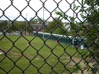 Porto-potties from through a fence.